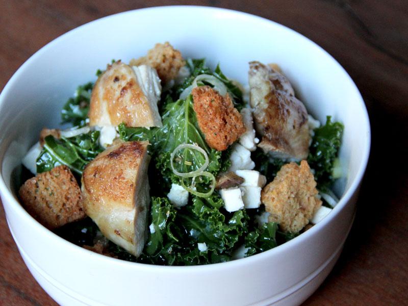 Salade de kale, hauts de cuisse de poulet, croûtons de pain à l'ail, vinaigrette à huile de truffe blanche
