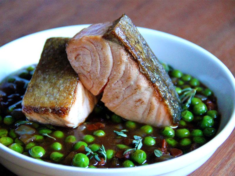 Saumon basse température, caramel au sirop d'érable aux agrumes, petits pois, lardons et estragon