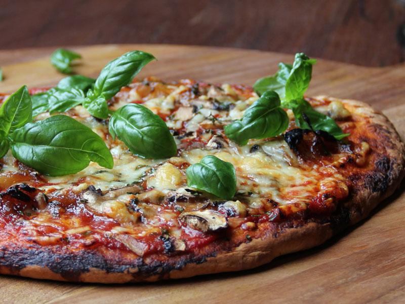 Pizza tomatée, basilic, oignons caramélisés, champignons, mozzarella